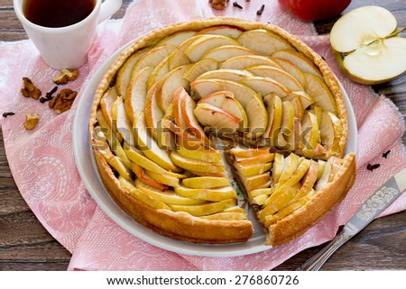 Apple tart, shortcrust pastry pie with walnuts on a wooden background - stock photo