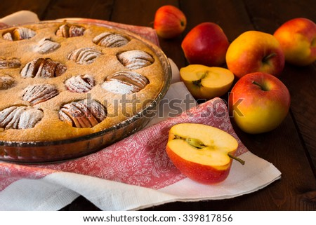 Apple tasty traditional homemade delicious breakfast baking pie tart sweet dessert in a baking dish, and apples on dark background, selective focus. Pastry. Dessert. Apple Pie. Apple Tart. Pie. Tart  - stock photo