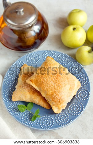 apple turnovers on plate with raw apple - stock photo