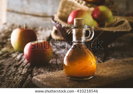 Apple vinegar. Bottle of apple organic vinegar on wooden background. Healthy organic food. - stock photo