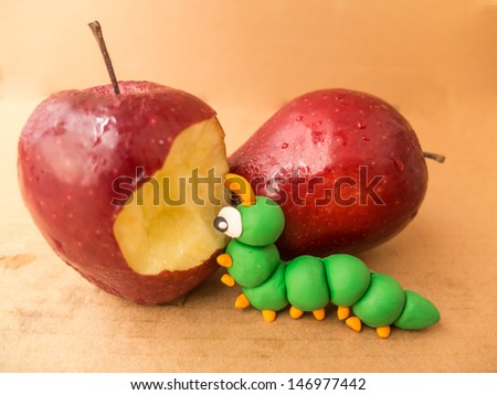 apple with a bite out of it showing a plasticine worm on brown paper background - stock photo