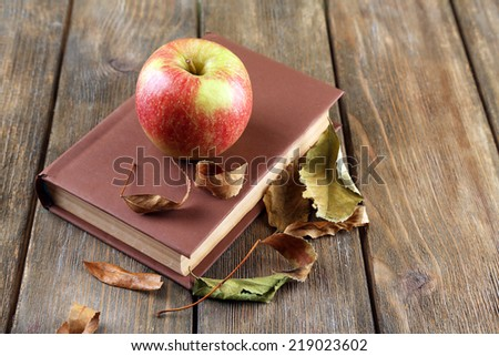 Apple with book and dry leaves on wooden background - stock photo
