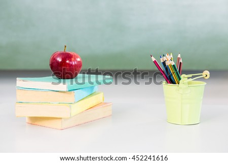 Apple with books and desk organizer on table in classroom