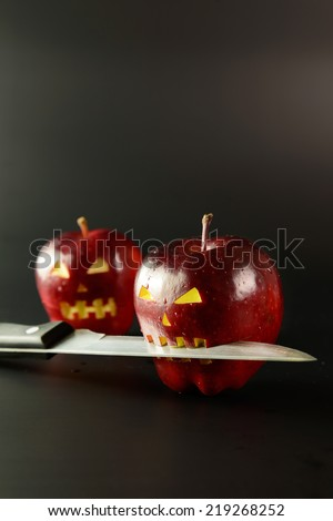 Apple with horror face and knife on it over black background - stock photo