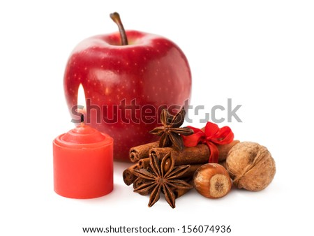 apple with nuts, star anise , cinnamon and a candle isolated on white
