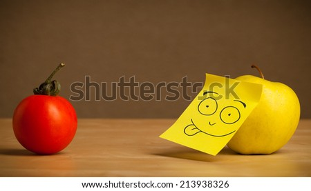 Apple with sticky post-it note showing tongue to tomato