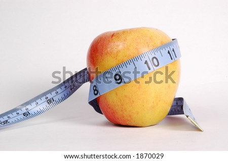 Apple wrapped with measuring tape. Concept of healthy, nutritious eating reduces waistline.