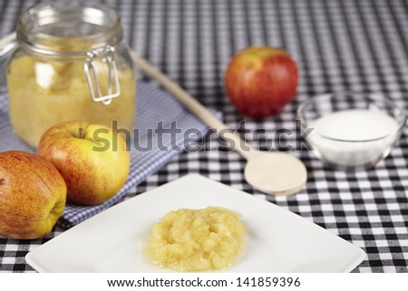 Apples, a wooden spoon, a small bowl of sugar and a bottling jar of stewed apples a ready on a black and white checkered tablecloth.