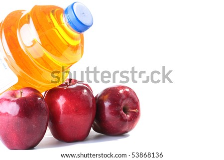 Apples and apple juice in the big plastic transparent container.