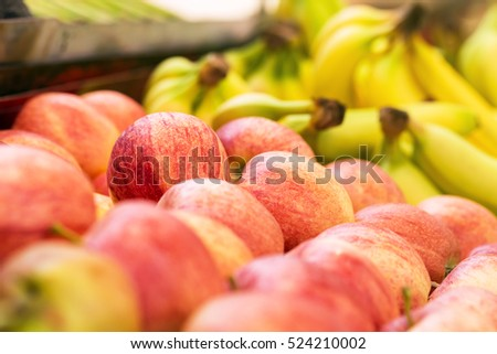 Apples and bananas on sale at grocery market, shallow depth