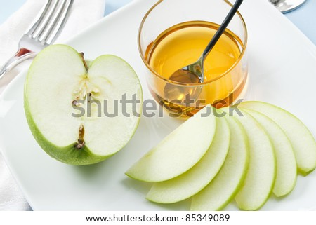 Apples and Honey are traditional symbols shared at Rosh Hashanah celebrations - stock photo