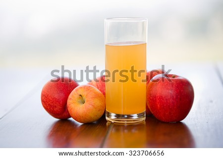 apples and juice on a wooden table, outdoor - stock photo