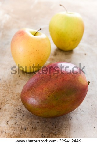 Apples and mango on rustic wooden board - stock photo
