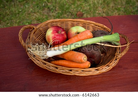 Apples and vegetables in a basket with wood texture background - stock photo