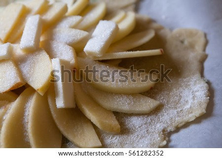 Apples arranged on olive oil dough, sprinkled with sugar
