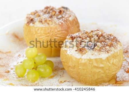 Apples baked with cottage cheese and raisins, decorated with nuts, cinnamon and powdered sugar - stock photo