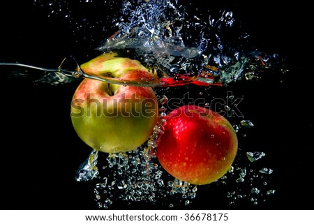 Apples falling to the water with splash and drops - stock photo