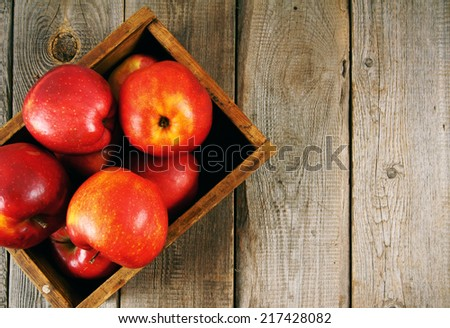 Apples in a box on a wooden background. - stock photo