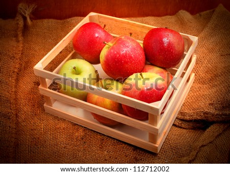 Apples in the box on the gunny bag isolated on wooden background