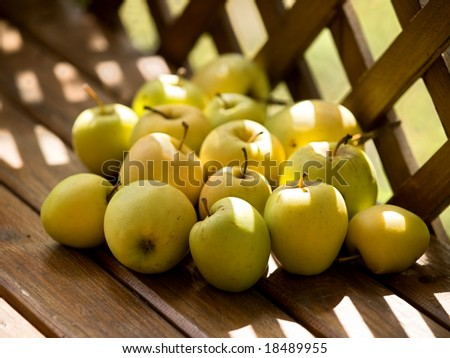 Apples on a old brown wooden bench - stock photo