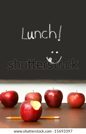 Apples on top of school desk with chalkboard in background - stock photo
