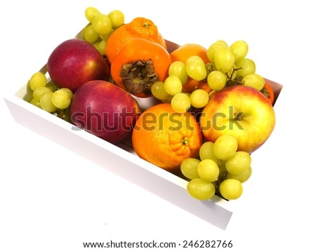 Apples persimmon fruits minneolas grapes and oranges in a box - stock photo