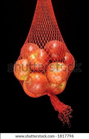 Apples suspended in a red net sack - stock photo