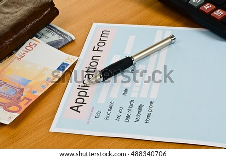 application form is on the table. On the table are: pen, calculator, money, leather purse