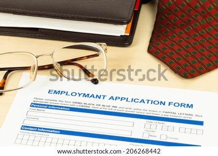 Application form, neck tie, glasses, and planner - stock photo