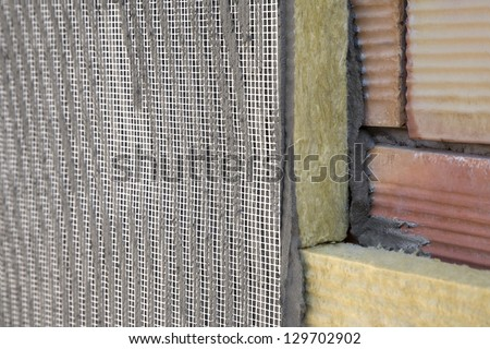 application of coating over insulation, brick wall, batting - stock photo