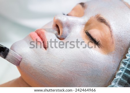 Application of the silver mask on the face of the girl. Cosmetic procedures for the face. Beautician facial treatment at a spa salon. The procedure to rejuvenate and nourish the skin of the face.  - stock photo