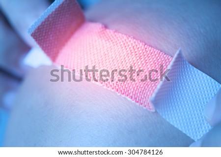 Applying adhesive bandage on knee - stock photo