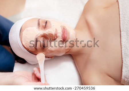 Applying facial mask at woman face at beauty salon - stock photo