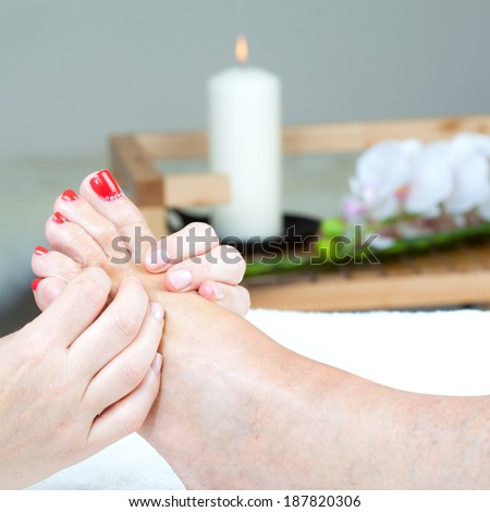 Applying foot massage in body care center - stock photo