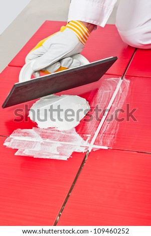 applying  grout whit rubber trowel red tiles - stock photo