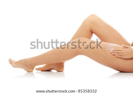Applying moisturizer cream on the legs