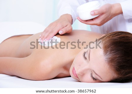 Applying  moisturizing cream on the female back before massage - close-up