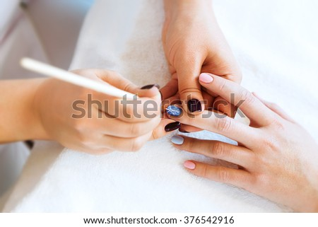 Applying nail polish on nails with a brush for applying nail polish on fingers. Close-up of beautician applying colorful varnish. Manicure nail applicator in a beauty salon. In a beauty salon varnish