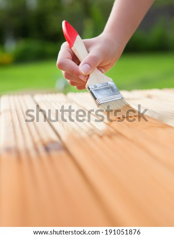 Applying protective varnish on a wooden furniture  - stock photo