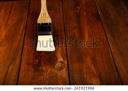 Applying protective varnish on a wooden table with brush - stock photo