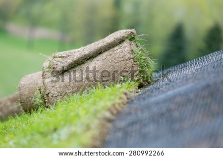Applying rolled green grass with erosion control mesh on a slope - stock photo