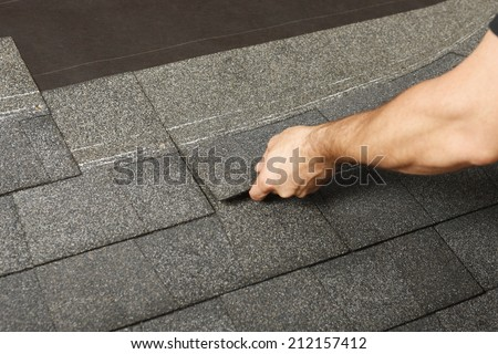 Applying roof shingles - stock photo