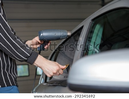 Applying tinting foil on a car window in a garage - stock photo