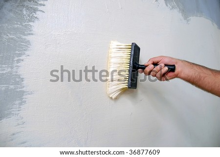 applying white parget on the wall with a brush