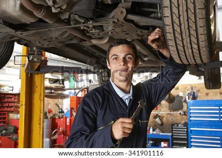 Apprentice Mechanic Working On Car - stock photo