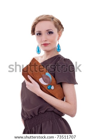 Approachable woman holding purse against blue background - stock photo