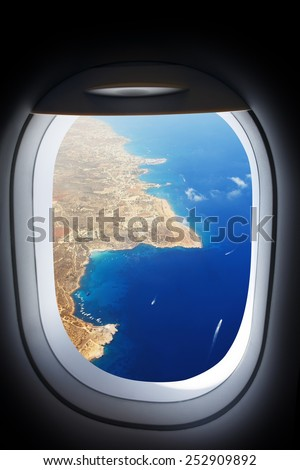 Approaching island holiday destination, jet plane window sea land view. Travel resort concept.  - stock photo