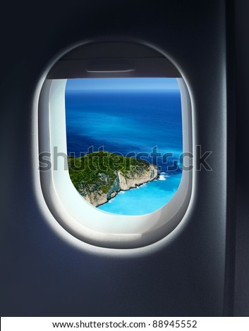 Approaching island holiday destination, jet plane window sky view