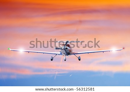 Approaching propeller aircraft seen from the front, against a vivid, radiant sky - stock photo