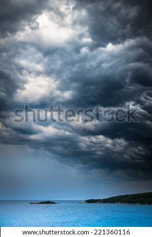 approaching storm weather over a turquoise Mediterranean sea and small islands - stock photo
